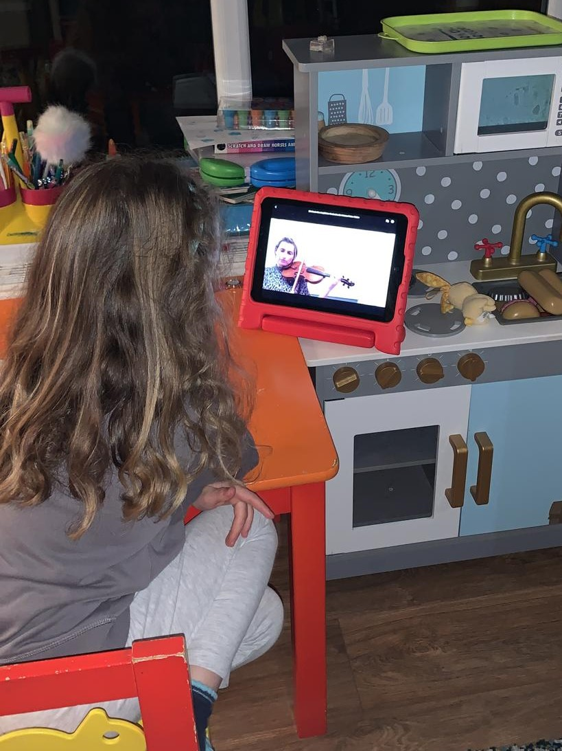 young girl watching webinar on tablet device