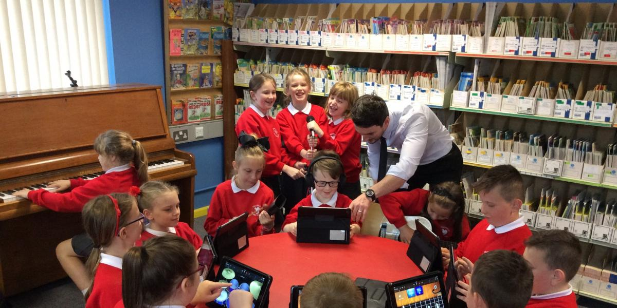 photo of children with tutor playing music on ipads