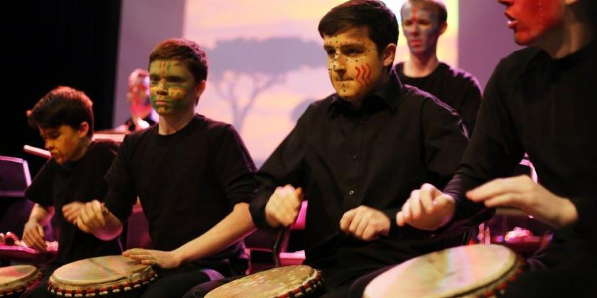 Image of African drumming workshop featuring pupils with facepaint